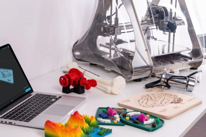 Notebook na stole vedle 3D tiskárny.